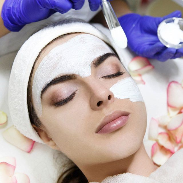 Cosmetologiest applies white mask on woman's face